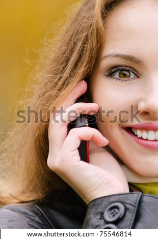 Half young beautiful woman smiles and talks on cellular telephone, close up, against yellow autumn nature. - stock photo