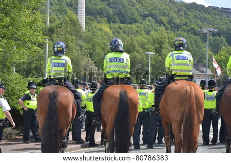 HALIFAX, WEST YORKSHIRE, ENGLAND-JUL 10: Riot Police on horses face demonstrators of the EDL (English Defence League) organised rally on July 10, 2010 in Halifax, West Yorkshire