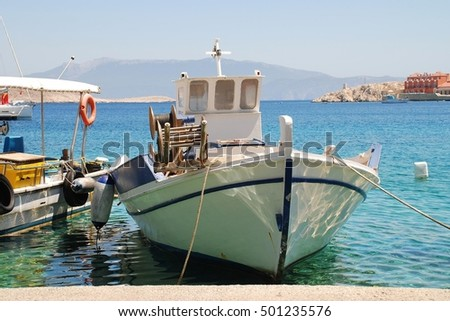 HALKI, GREECE - JULY 25, 2016: Fishing boats moored in Emborio harbour on the Greek island of Halki. The main industries of the small Dodecanese island are fishing and tourism.