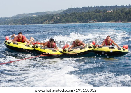 HALKIDIKI, GREECE- MAY 26, 2014: Group of unrecognized people bouncing up over wake on tubes. 20 million tourists expected to visit the beaches, making it a record, in Halkidiki, Greece.