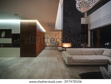 Hall in a cottage with light walls. On the right there is a beige sofa with a pillow and a dark table with decorative vases, two black armchairs behind the sofa. Under them there is a carpet. Over the - stock photo