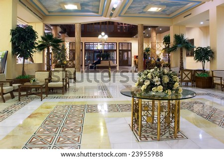 Hall in hotel with marble floor and flowers on the table