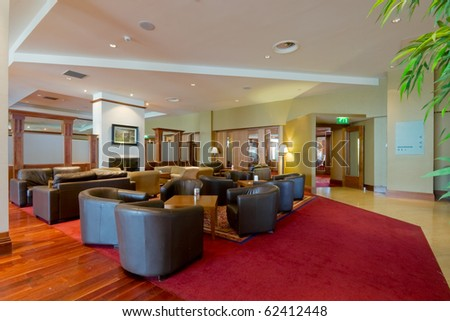 hall with leather arm-chairs and red carpet in modern Hotel interior