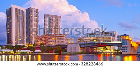 Hallandale Beach Florida, modern buildings and colorful illuminated bridge at sunset - stock photo