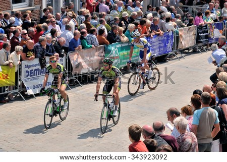 HALLE, BELGIUM-JUNE 24, 2015: Participants of cycling race cross historical center of Halle - stock photo