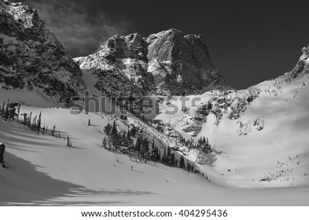 Hallett Peak in Rocky Mountain National Park looms over a frozen and snow covered Emerald Lake - stock photo