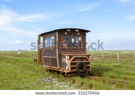 HALLIG LANGENESS, GERMANY - MAY 25. Railcar to transport tourists and freight from  Langeness to mainland and return on May 25, 2014. The railway leads up on a causeway from Langeness to mainland - stock photo