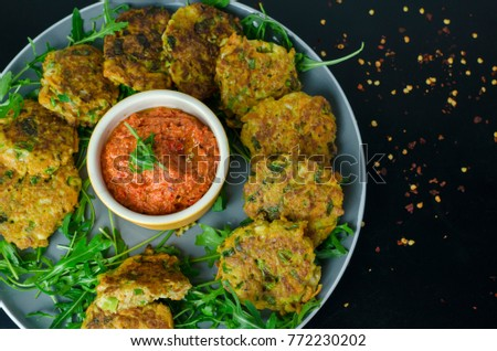 Halloumi Carrot Fritters with Roasted Red Pepper and Cashew Dip with chili flakes on a black table, top view