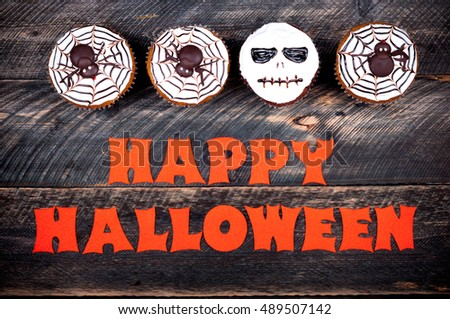 Halloween background. Funny pumpkin cupcakes with spiders and scull for halloween party on old rustic wooden table. Top view