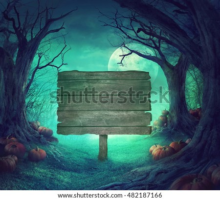 Halloween background. Spooky forest with dead trees and pumpkins.Halloween design with pumpkins. Wood sign