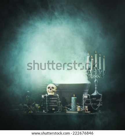 Halloween background with a lot of different witchcraft tools: skull, candles, book, poison and smoke - stock photo