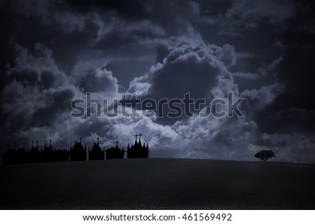 Halloween background with empty plain in the foreground, lonely tree and silhouette of old european cemetery on the horizon against dramatic cloudy sky.