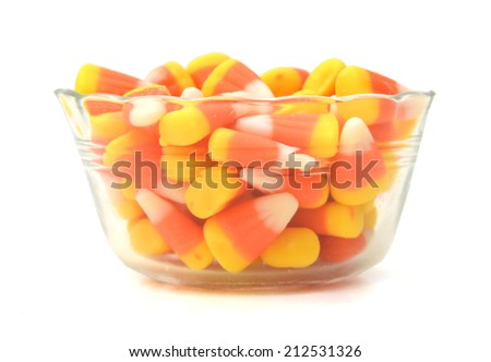 Halloween candy corn in glass bowl isolated on white background. Closeup  - stock photo
