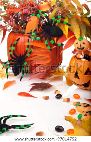 Halloween candy scattered around, fall beries, leaves and spiders. - stock photo
