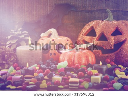 Halloween Candy with pumpkins, Jack O Lantern, candles and bats on dark wood background, with added vintage style filters and lens flare.  - stock photo