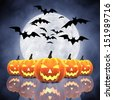 Halloween carved pumpkins ,full moon and bats on blue background - stock photo