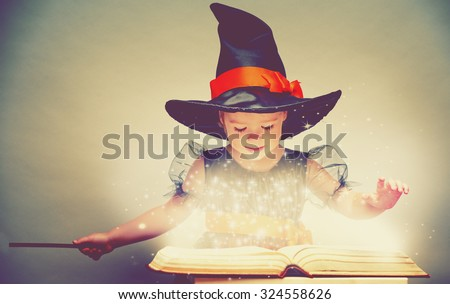 Halloween. cheerful little witch with a magic wand and glowing book conjure and laughs. - stock photo