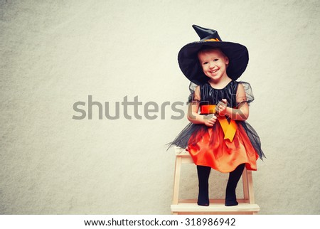 Halloween. cheerful little witch with a magic wand conjure and laughs. - stock photo