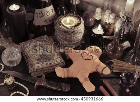 Halloween close up of voodoo doll, tarot cards, candles, vintage bottles and magic objects. Divination rite.There is no foreign text in the image, all symbols are imaginary and fantasy ones. - stock photo
