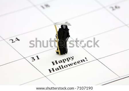 "Halloween concept. A miniature grim reaper holding a scythe is standing on a calendar date that says ""Happy Halloween."" - stock photo"