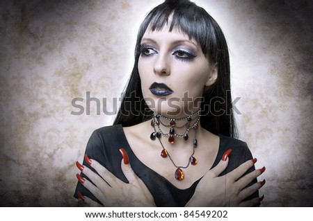Halloween concept. Fashion portrait of gothic style woman night vampire or evil witch in black dress and vintage necklace. Brunette with long health hair. - stock photo