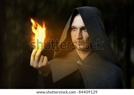 Halloween concept. Powerful Male witch or wizard with fire in hands. Ball from fire burns. Fantasy magic