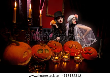 Halloween concept: sexy ladies vampire with halloween pumpkins over red background - stock photo