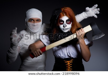 Halloween concept with mummy and woman with axe - stock photo