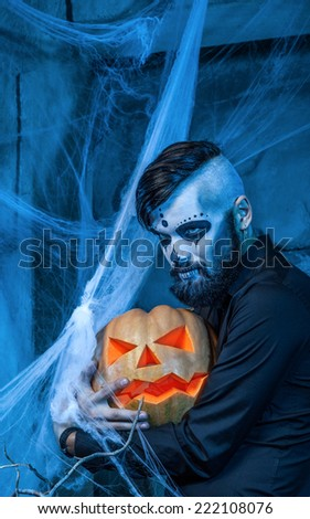 Halloween concept with young man in day of the dead mask face art.  - stock photo
