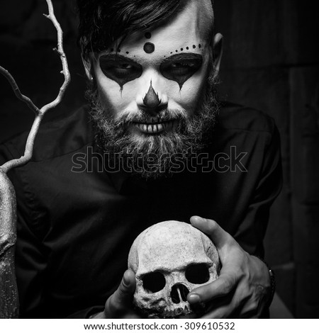 Halloween concept with young man in day of the dead mask face art.