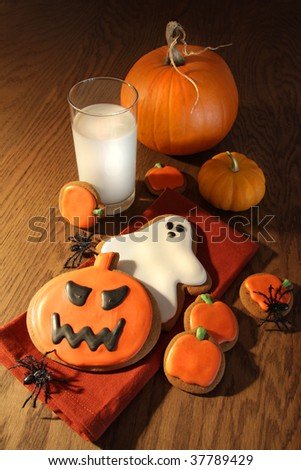 Halloween cookies with pumpkins and a glass of milk - stock photo
