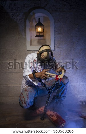 halloween costume, Man chained with blood and knife, has a severed leg blood - stock photo