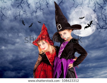 halloween costumes kid girls on moon night sky with bats [photo-illustration] - stock photo
