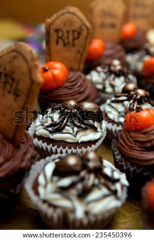 Halloween cup cakes with spiders, pumpkins and graves. seasonal treat for trick or treat. buttercream bakery  - stock photo