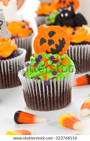 Halloween cupcake with jack-o'-lan�·tern and bat decorations surrounded by Halloween cupcakes, corn candies, and decoration. - stock photo