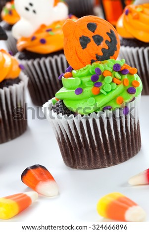 Halloween cupcake with jack-o'-lan·tern and bat decorations surrounded by Halloween cupcakes, corn candies, and decoration.  - stock photo