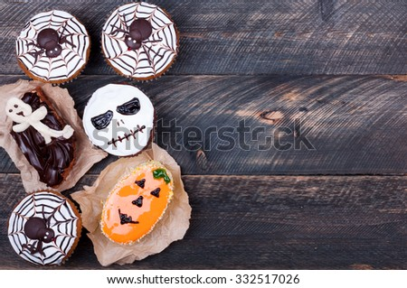 Halloween cupcakes decorated with icing on old wooden background. Halloween background. Lots of copy space. Top view - stock photo