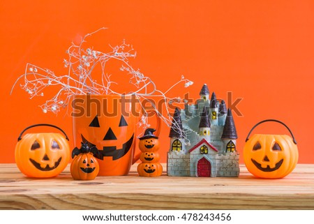 Halloween decoration on wooden table over orange background