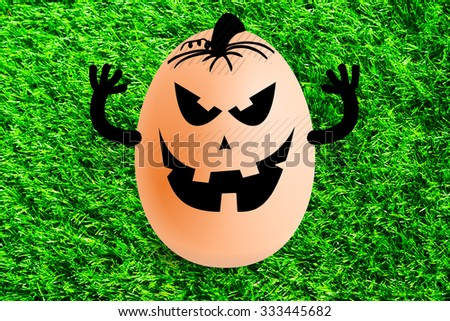 Halloween egg on green grass background - stock photo
