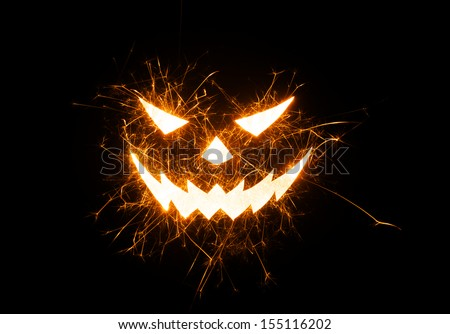 Halloween evil face image in fiery flying sparks on black background with copy space. - stock photo