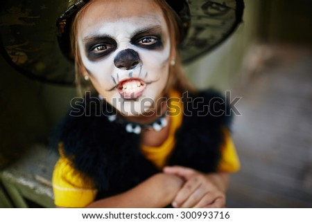 Halloween girl with painted face looking at camera - stock photo