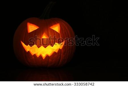 Halloween glowing pumpkin on black background - stock photo