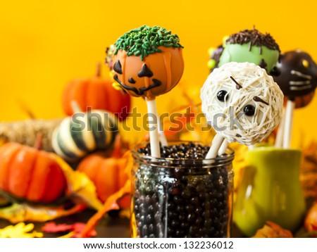 Halloween gourmet cake pops with holiday decor on orange backround. - stock photo