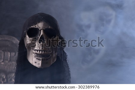 Halloween grim reaper prop with scary faces in smoky background - stock photo