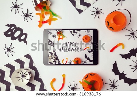 Halloween holiday background with digital tablet and decorations - stock photo