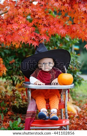 Halloween holiday. little girl blonde in a black hat sitting at a table next to a pumpkin in the garden - stock photo
