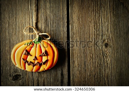 Halloween homemade gingerbread cookie over wooden background - stock photo