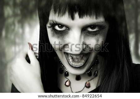 Halloween horror concept. Fashion portrait of witch or night vampire woman. Dark gothic makeup - stock photo