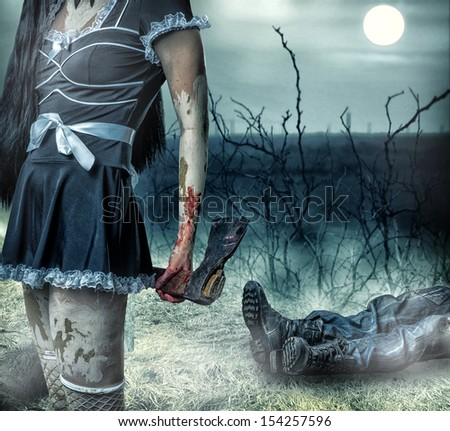 Halloween horror concept. Woman zombie holding axe in hands. In the background lies the  legs of corpse man - stock photo