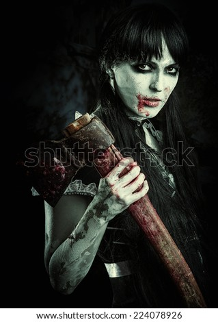Halloween horror. Scary zobie woman holding bloody axe in dirty hand - stock photo